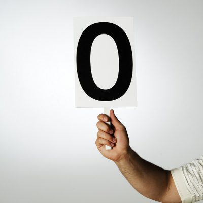 Male hand holding up a sign with a zero or O on it.