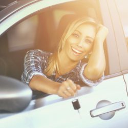 Smiling cheerful blond woman in her new car.She's leaning through car window and happily facing camera and showing car keys.She has blond hair pulled back with a clip.Wearing blue square pattern shirt. It's summer sunset with sunlight coming into the frame from the right hand side.